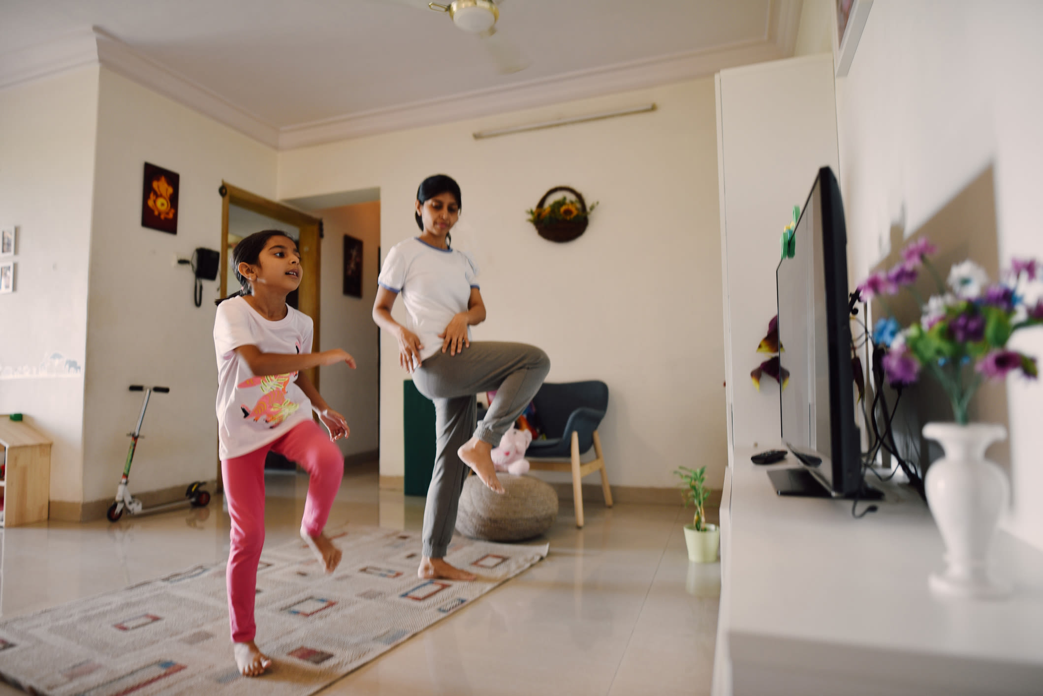 A mother and her daughter doing exercise at home