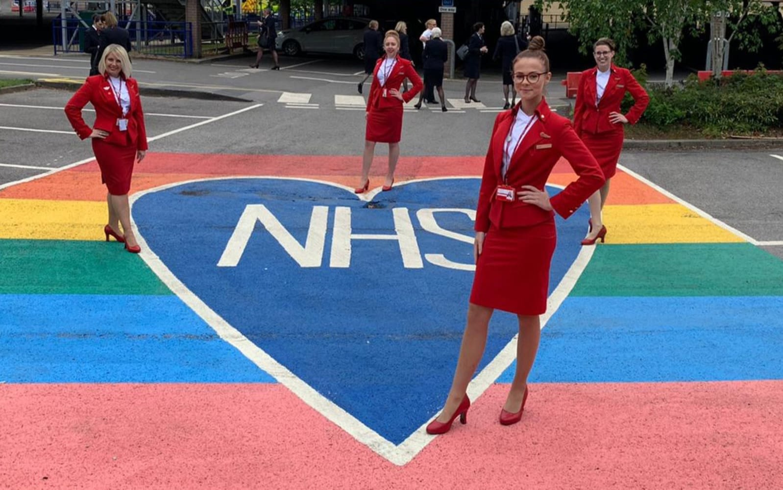 Virgin Atlantic crew pose with a large chalk rainbow heart with the NHS emblem across it.