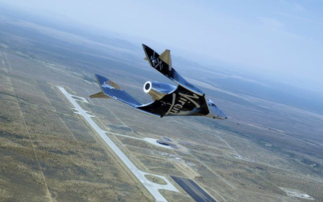 Virgin Galactic flying across land with blue sky