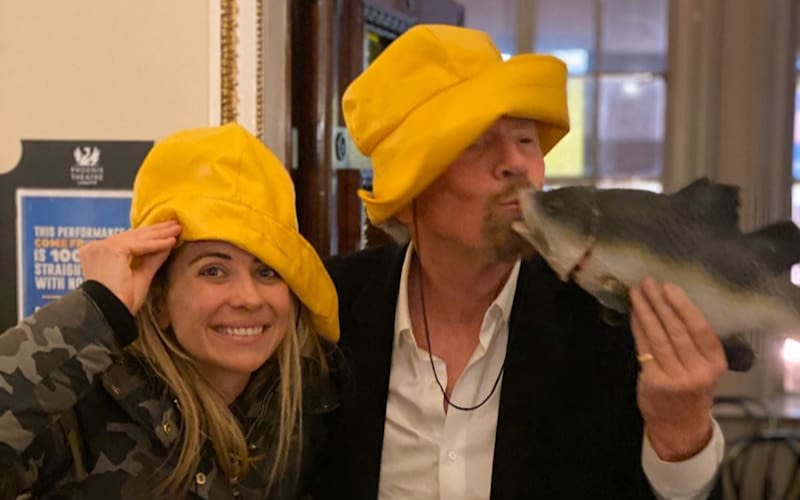 Holly and Richard Branson wearing yellow fisherman hats and Richard is kissing a plastic fish