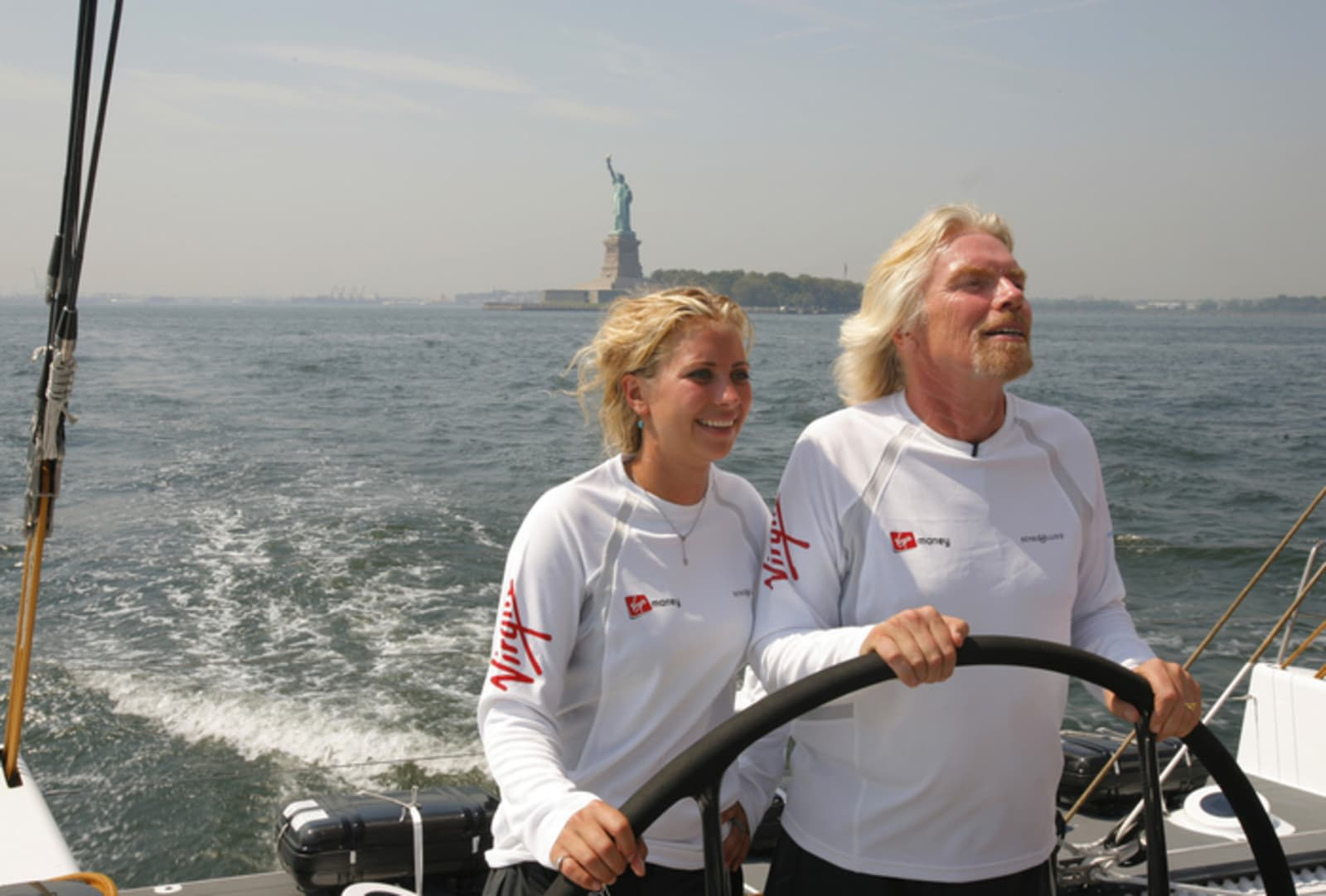 Richard and Holly Branson sailing boat in Virgin Money Sail Challenge. Statue of Liberty in background.