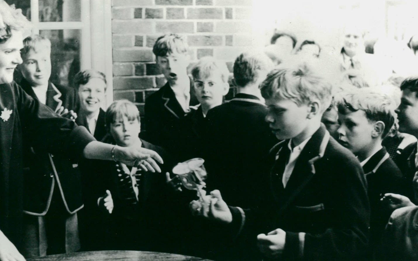 A black and white photo of a young Richard Branson in a group at school being handed a trophy