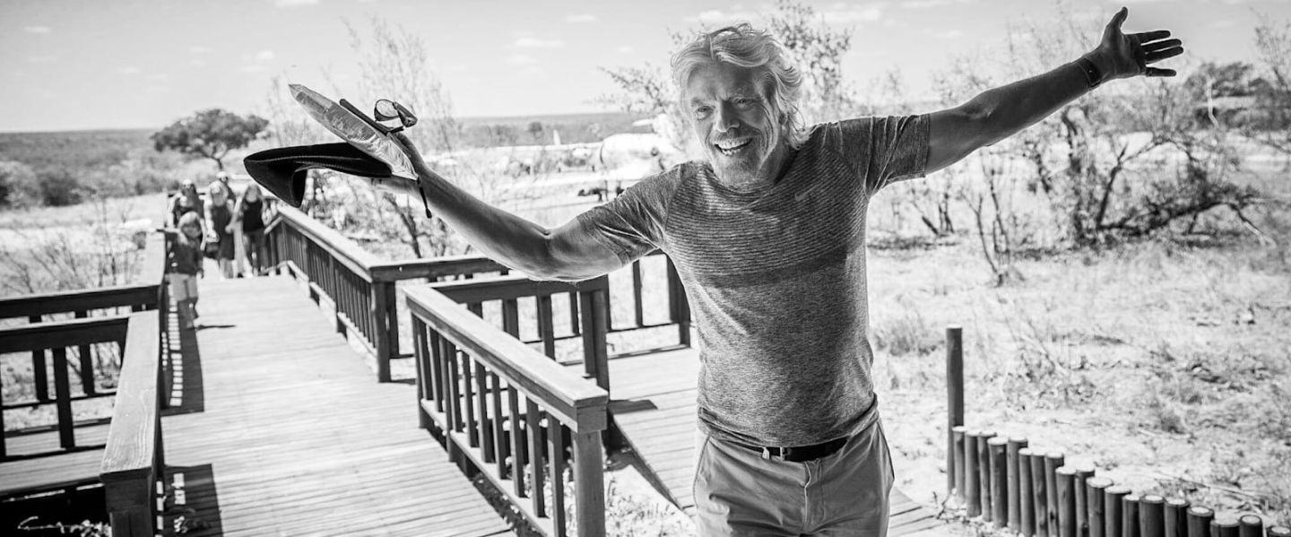 Black and white image of a smiling Richard Branson with his arms wide open
