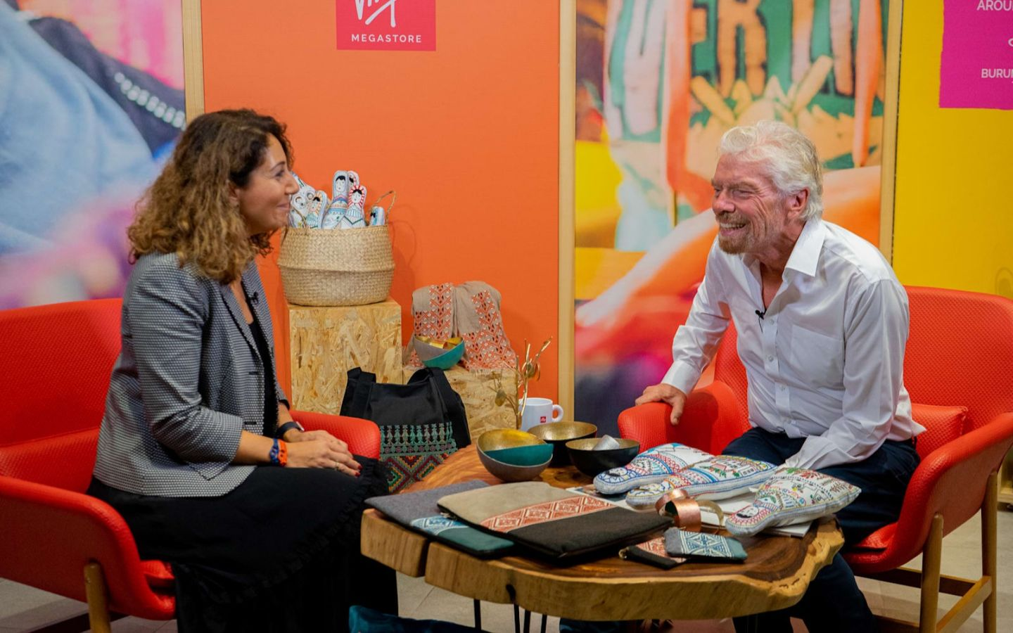 Richard Branson sat down with a lady laughing with a table of stock in front of them for Virgin Megastore in Dubai