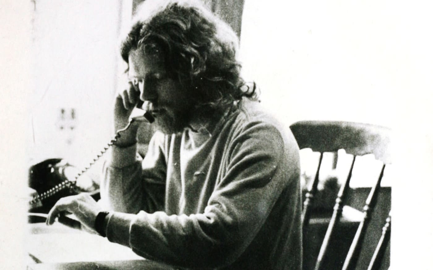 Black and white photo of Richard Branson in his 20s, sat at a desk, on the phone