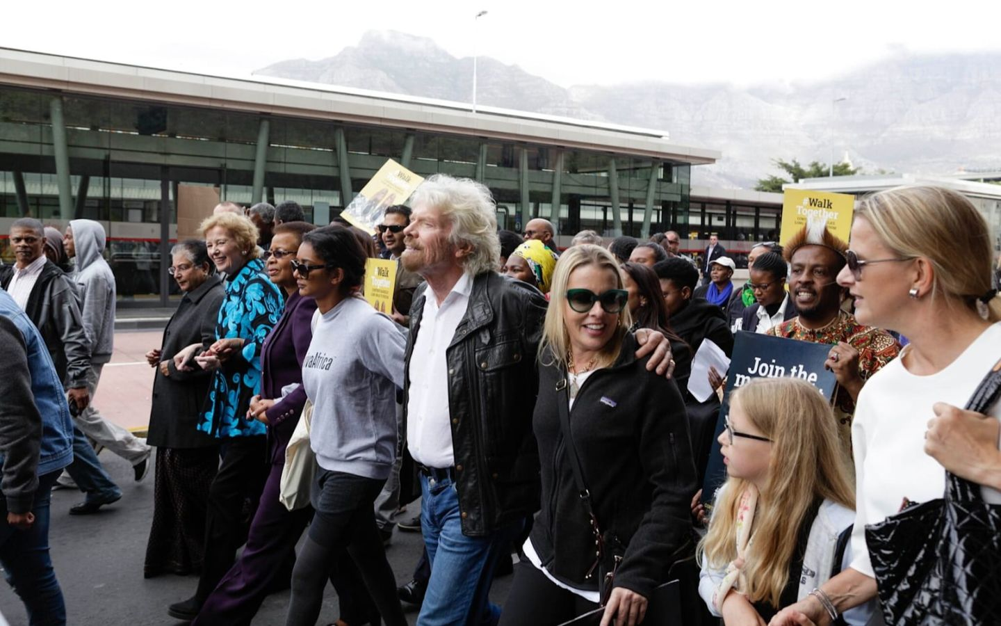 Richard Branson walks with a large group  of people.  He is wearing jeans, a black leather jacket and a white shirt