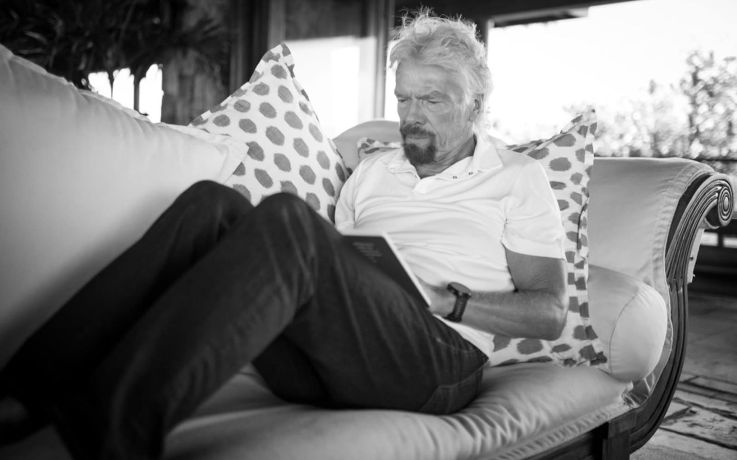 A black and white image of Richard Branson with his feet up on the sofa reading a book
