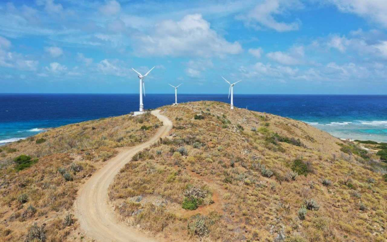 Three wind turbines on top of a small mountain overlooking the sea
