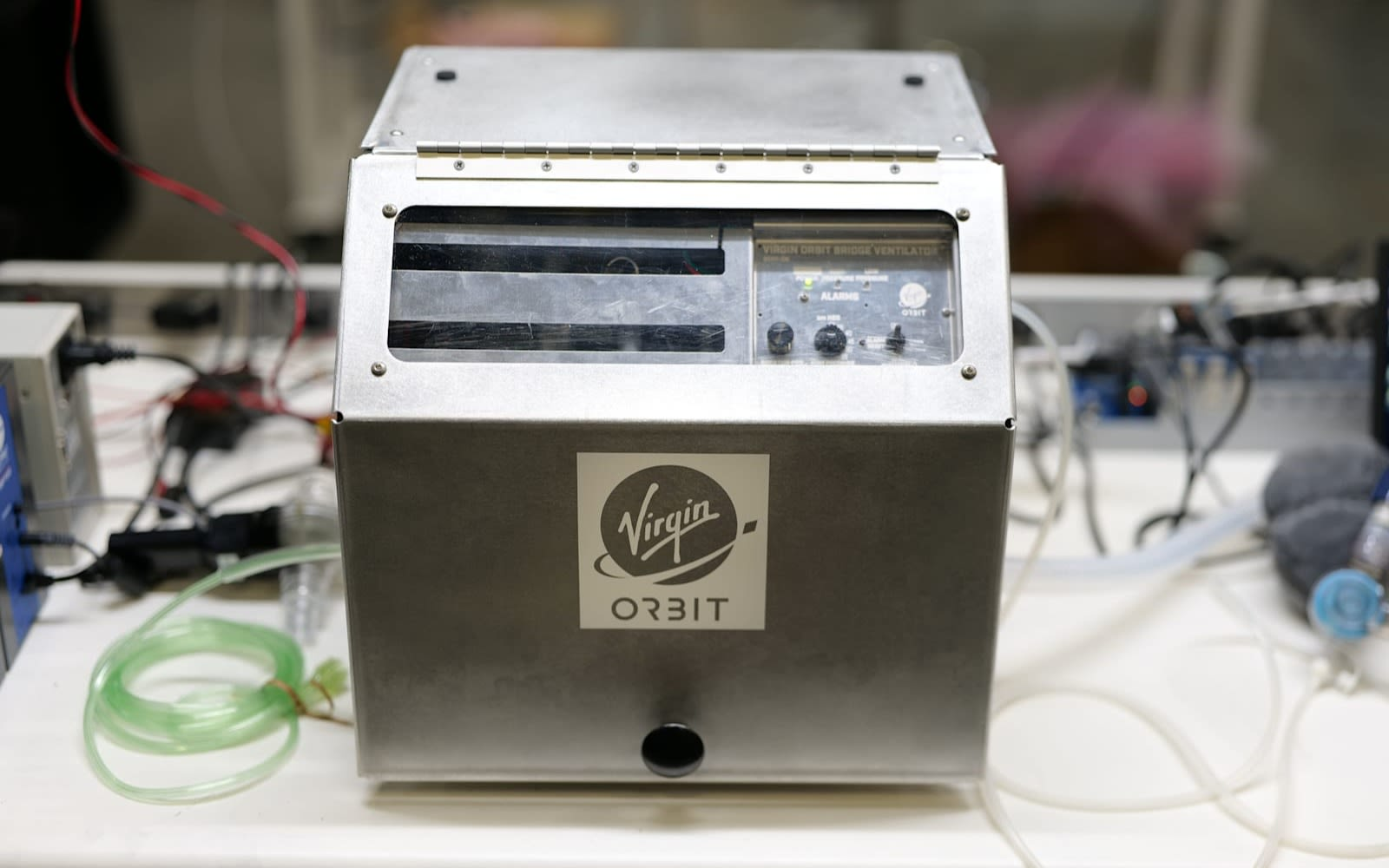 Silver cased ventilator on work bench with Virgin Orbit logo