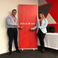 Alexander and Stephanie Florio next to a sign that says Pitch Day
