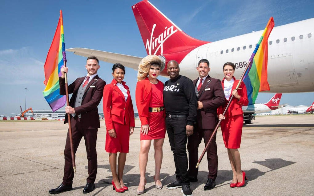 The crew for Virgin Atlantic's pride flight posing with LGBT+ flags