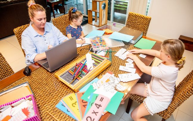 A woman on a laptop with her two daughters at the table homeschooling