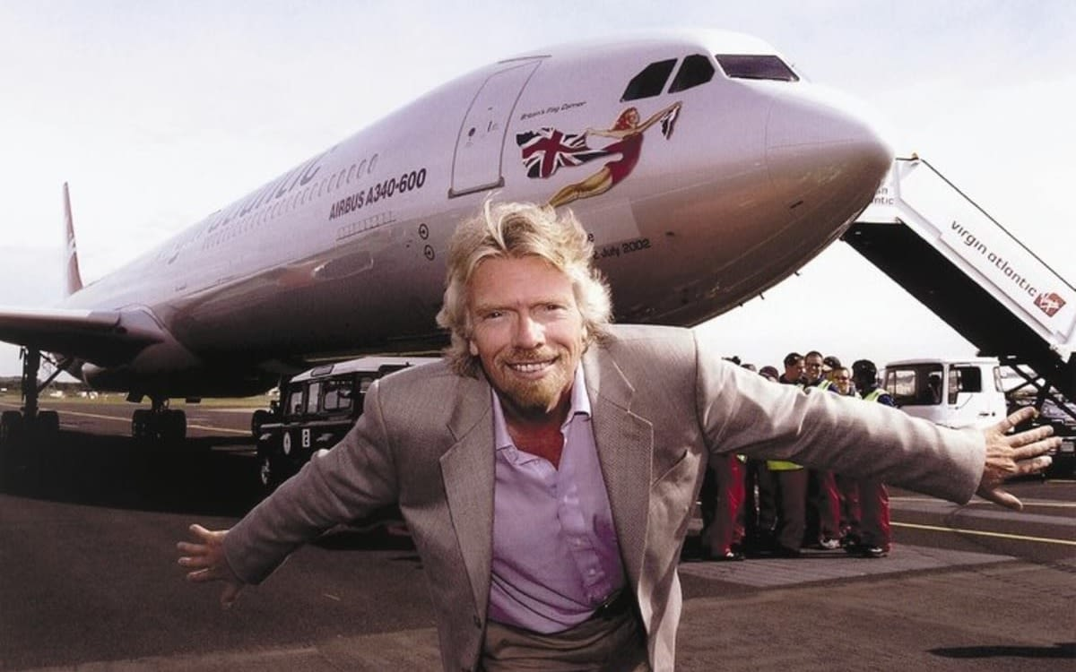 Richard Branson smiling in front of a Virgin Atlantic plane on the tarmac