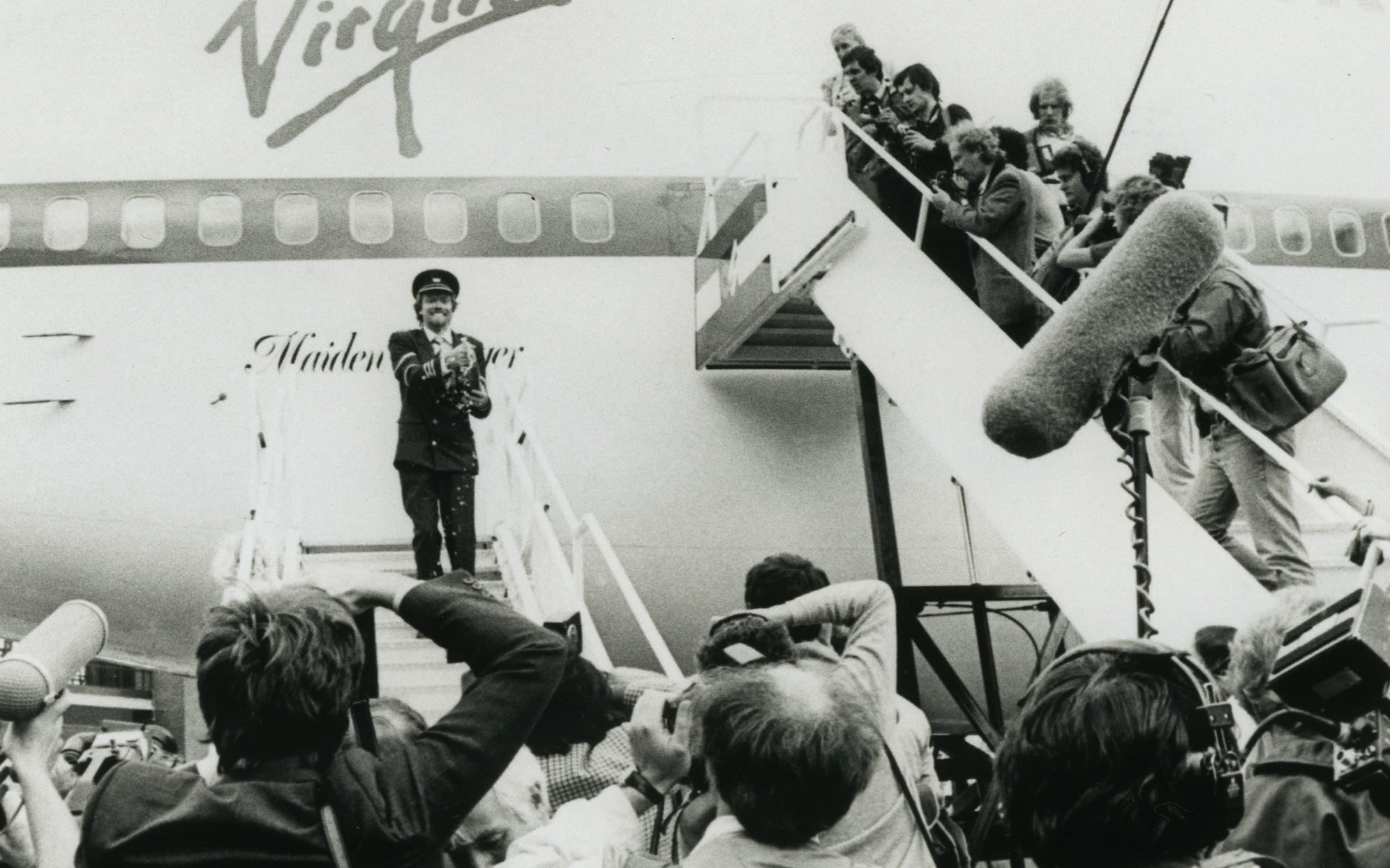 Richard Branson celebrating surrounded by the media in front of a Virgin Atlantic aeroplane