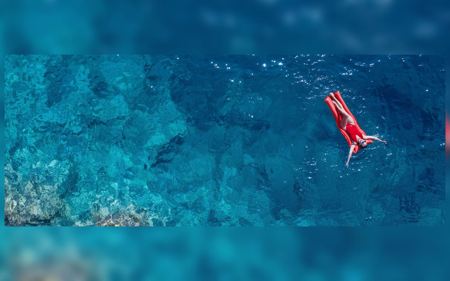 A person on a red lilo floating on a blue sea