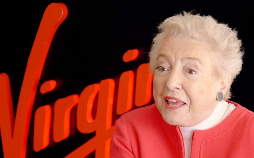 Dame Steve Shirley, talking, with the Virgin logo on a wall behind her