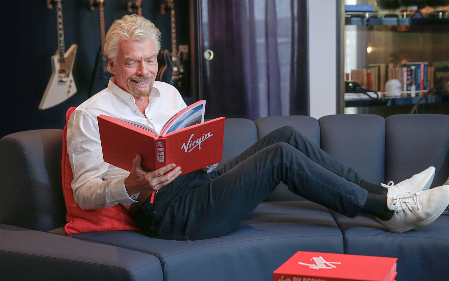 Richard Branson relaxing on a sofa reading a copy of Virgin By Design