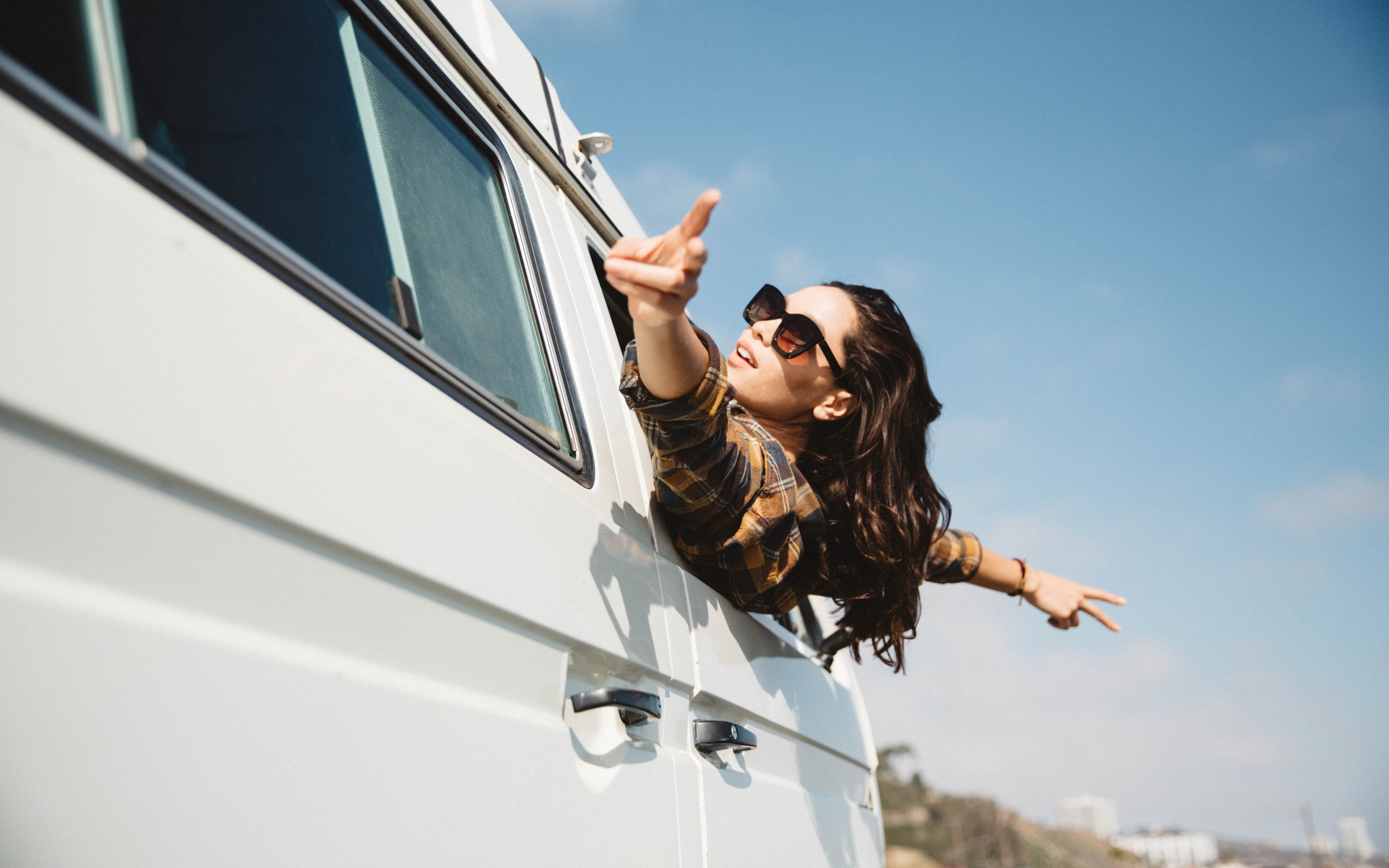 A woman leans out of a campervan with her hands in the air and her fingers making the peace sign