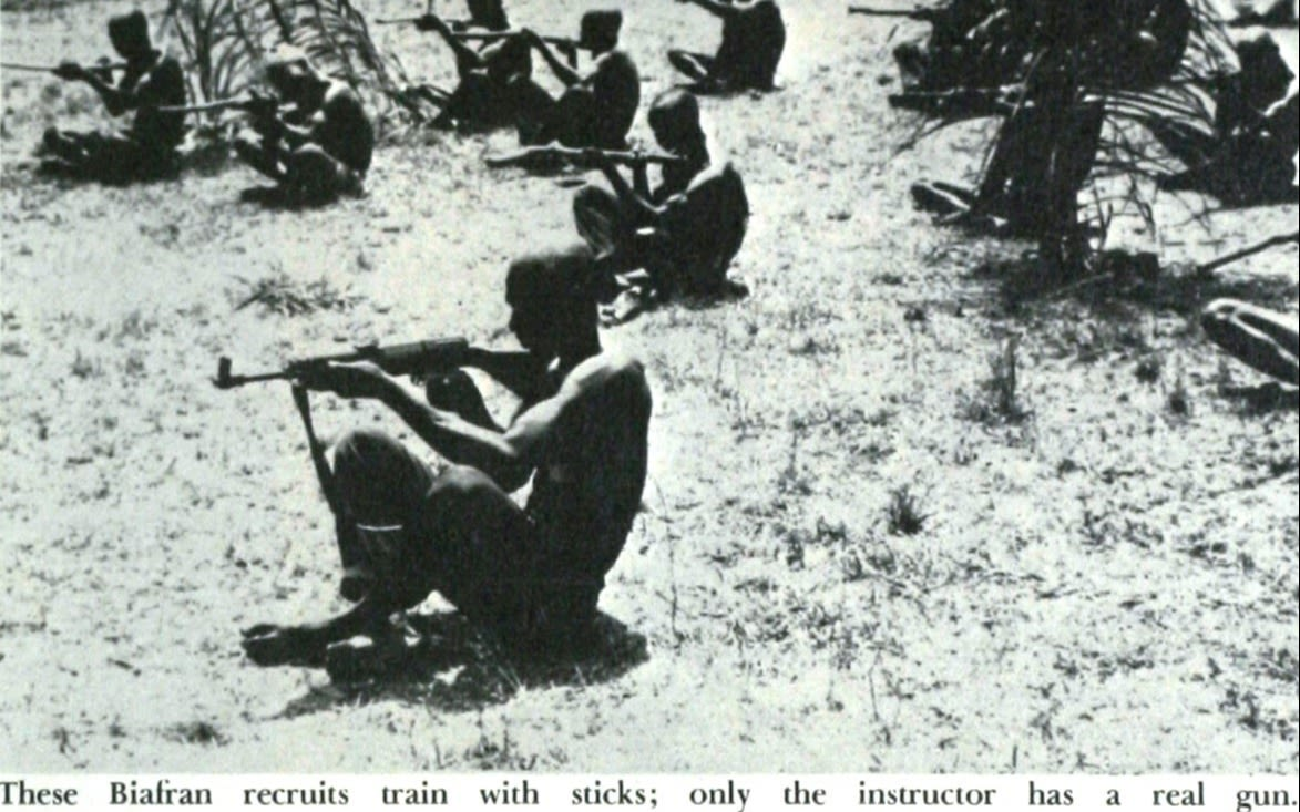 Black and white photo of a Biafra recruit training with a stick whilst sat on the ground