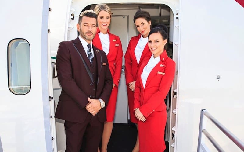 Four members of Virgin Atlantic cabin crew stand at the door of an aircraft