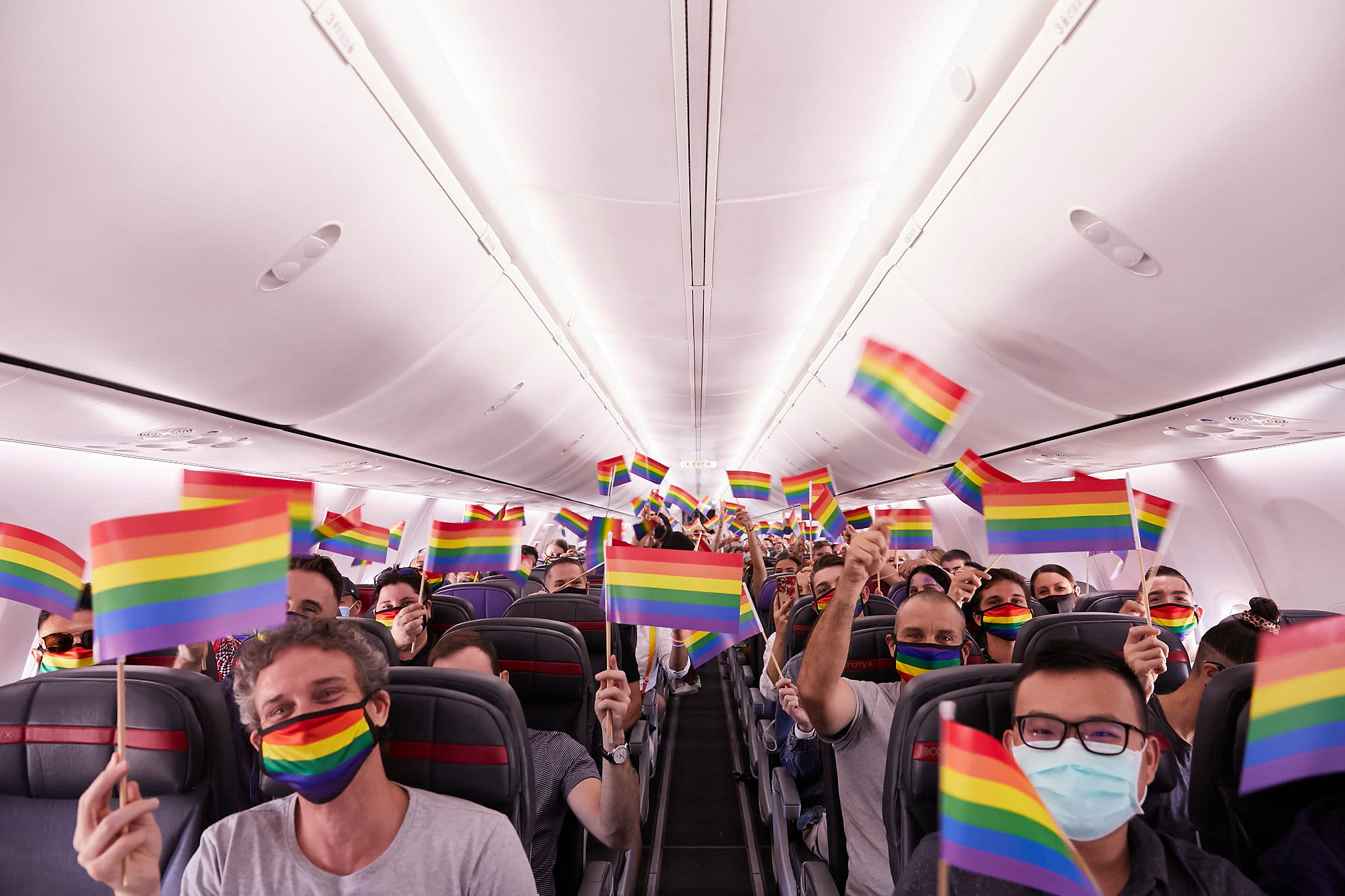 Passengers on Virgin Australia's Pride Flight wave rainbow flags