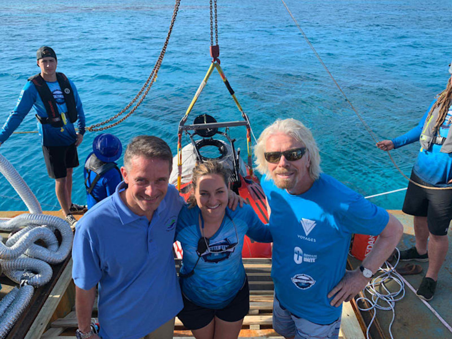 Richard Branson dressed in blue standing on a ship with four people