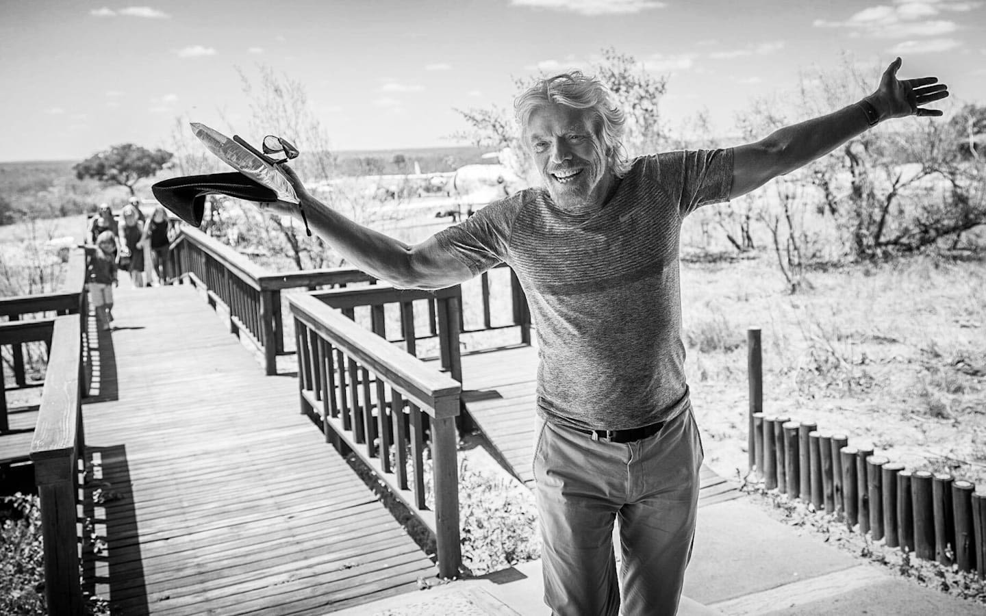 Black and white image of Richard Branson walking towards the camera, smiling, with his arms out wide