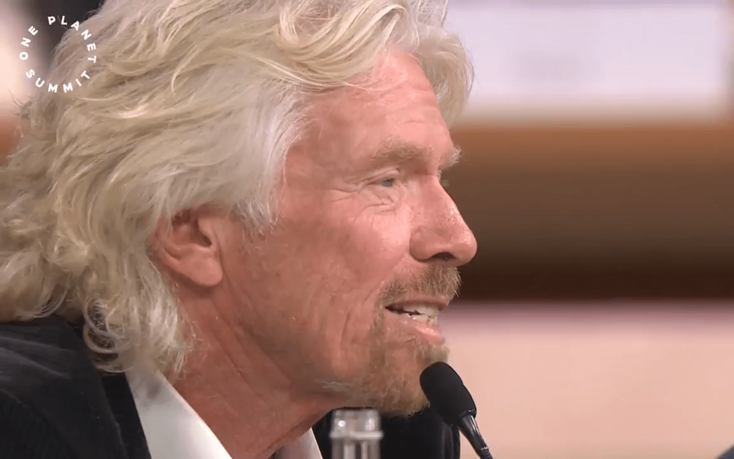 Richard Branson speaking into a microphone at the One Planet Summit
