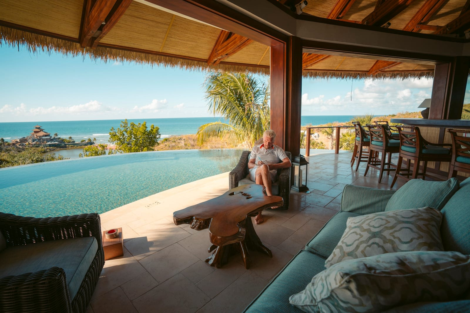 Richard Branson sitting in a chair by the pool on Necker Island writing