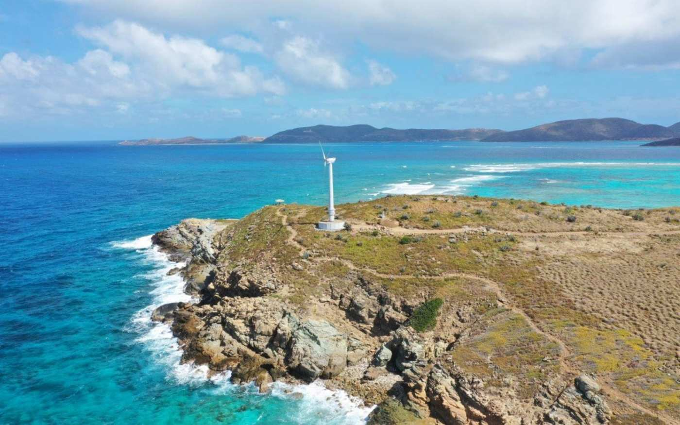 Wind turbine on the tip of an island, surrounded by sea, with other islands in the distance