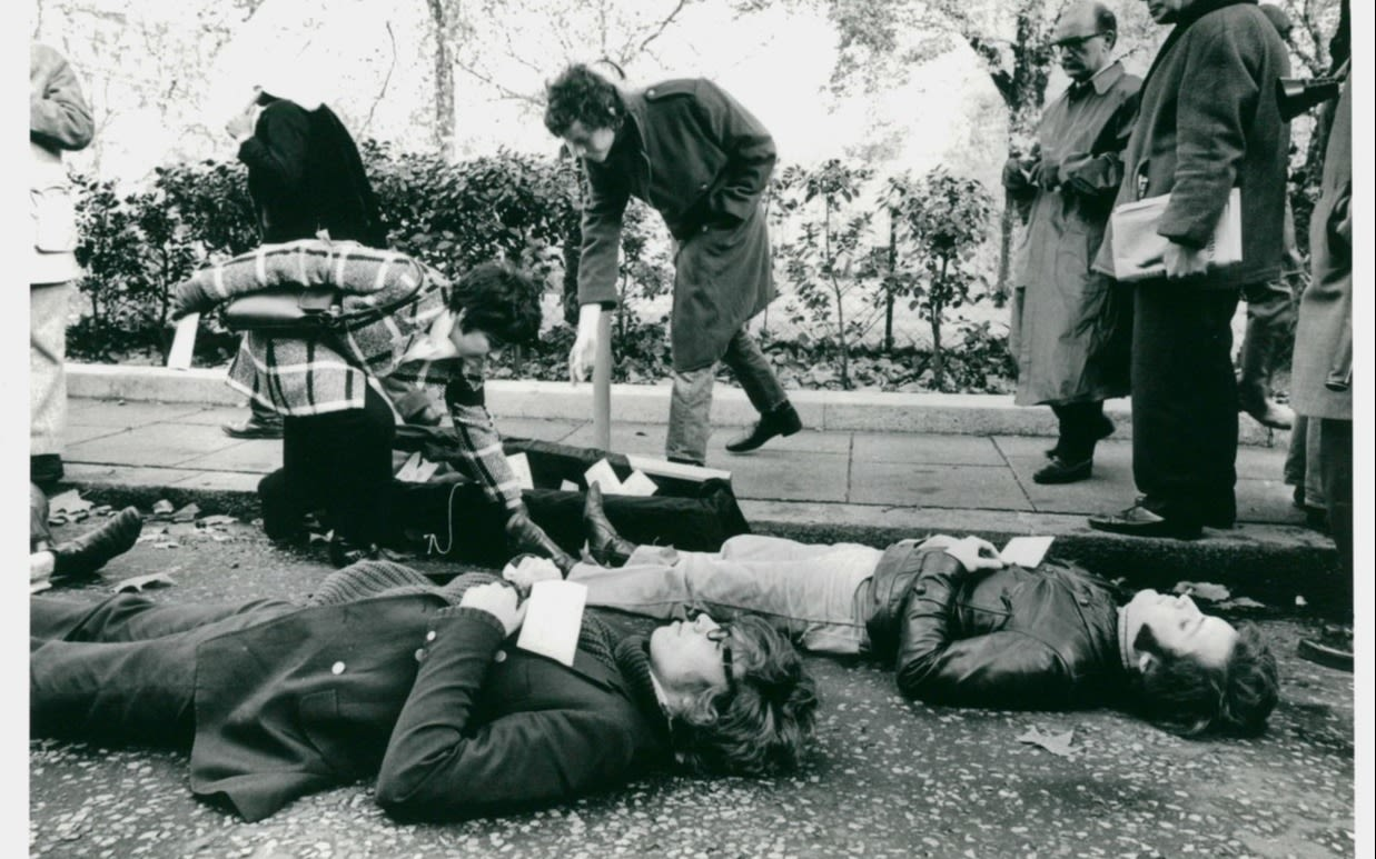 Black and white photo of students lying down on grass in protest