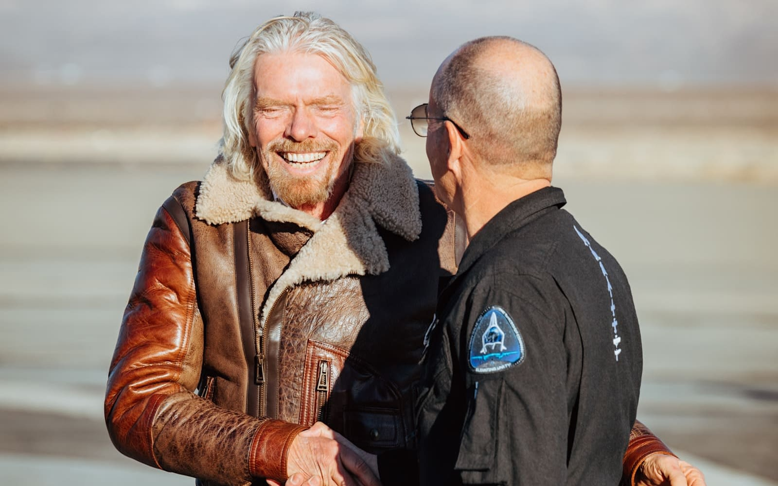 Richard Branson shakes hands with Virgin Galactic pilot Rick 'CJ' Sturckow after Virgin Galactic's first spaceflight