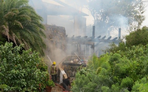 Fireman with a house to stop the fire on Necker Island