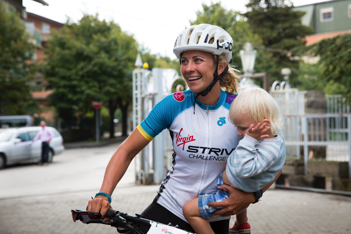 Holly Branson on her bike during the Strive challenge, pausing to hold one of her children
