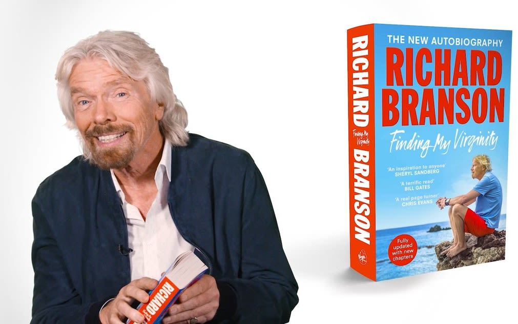 Richard Branson smiling with a copy of his autobiography - Finding My Virginity