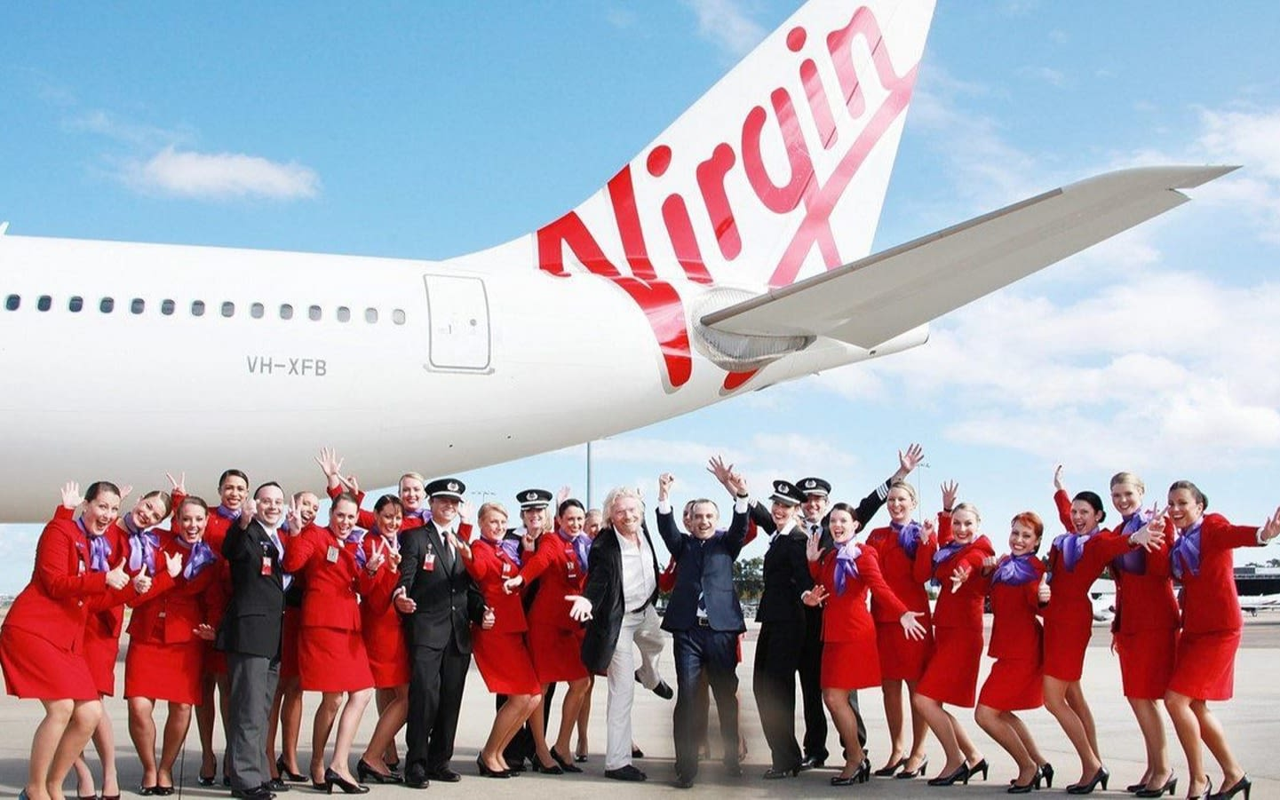 Richard Branson with a group of Virgin Australia cabin crew and pilots in fun pose with the tail end of a Virgin aeroplane behind them