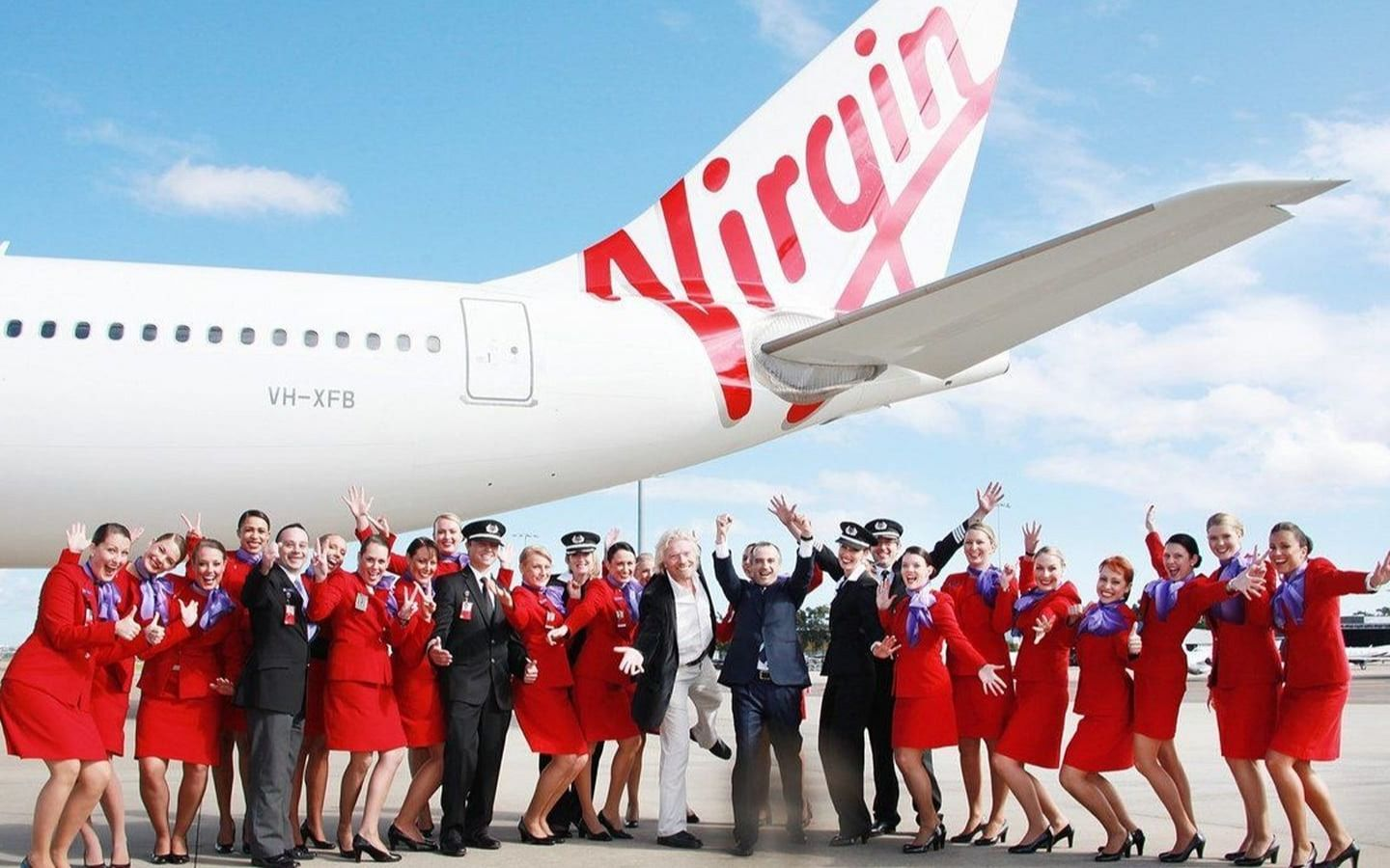 Richard Branson, Virgin Australia cabin crew and pilots stand with their arms in the air, smiling, in front of a Virgin Australia plane