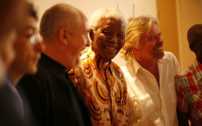 Richard Branson standing next to Nelson Mandela and others