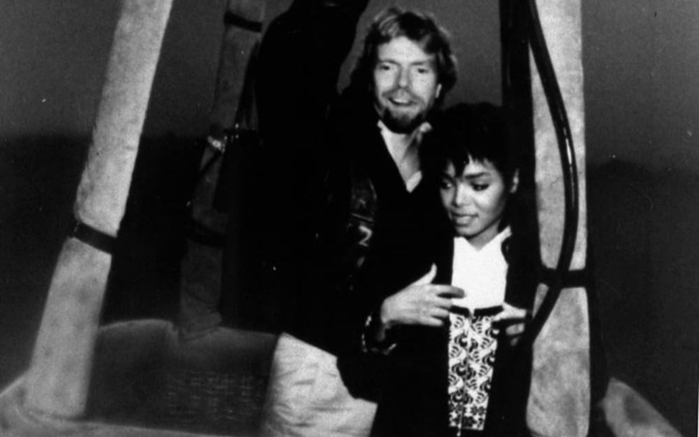A black and white photo of a young Richard Branson with Janet Jackson, in the basket of a Virgin Balloon
