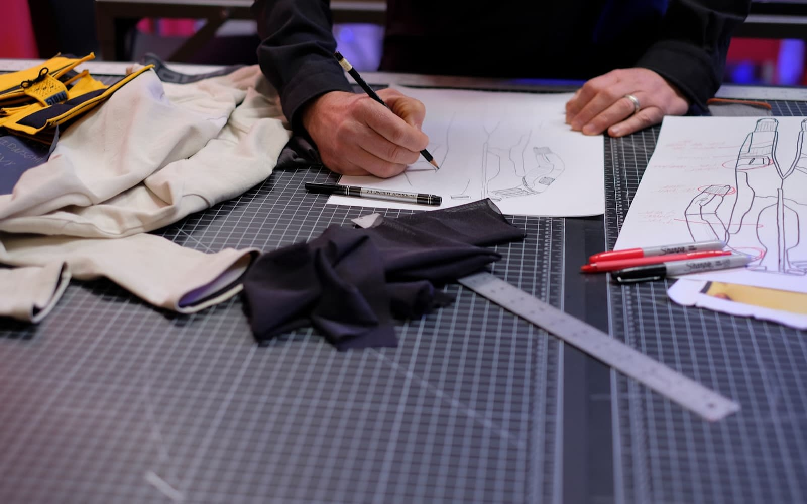 Design instruments on a table, with hands drawing clothing just in view