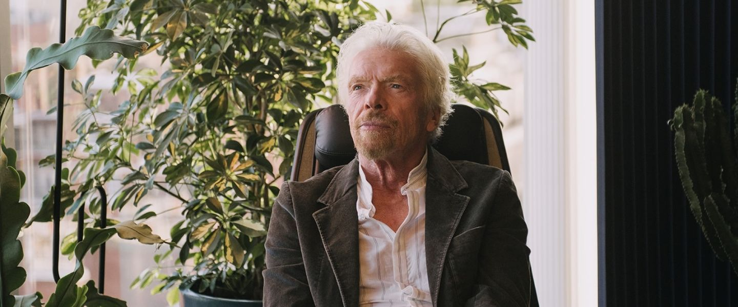 Richard Branson sat in chair with plants in the background