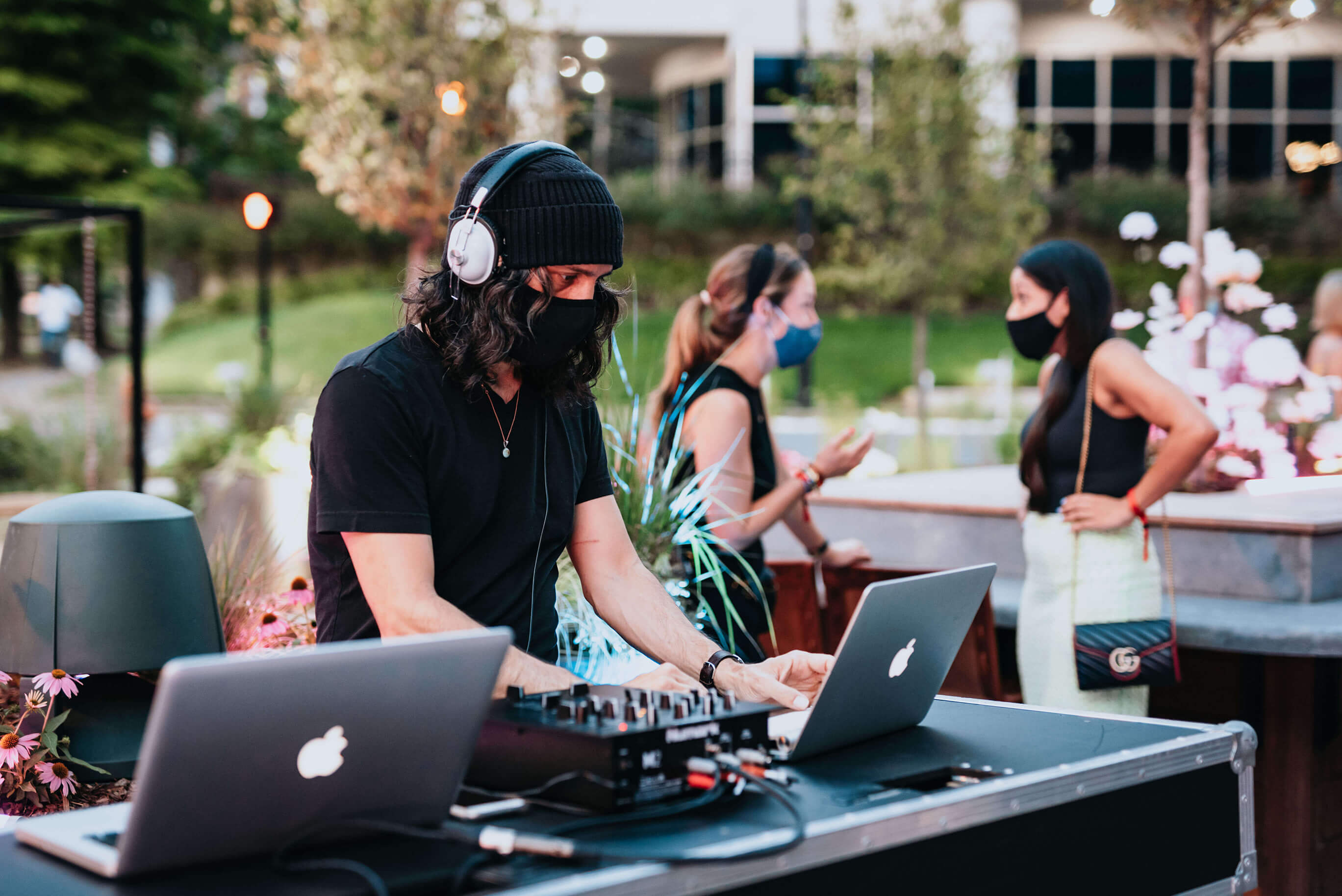 A man DJing with a facemask on with two women in the background chatting while wearing facemasks