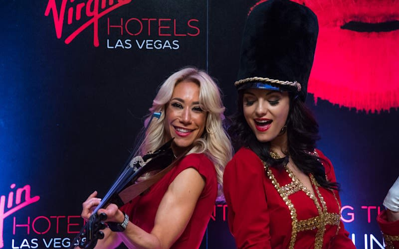 Two women stand back to back performing at the launch of Virgin Hotels Las Vegas, one of them wearing a bearskin hat whilst the other plays the violin