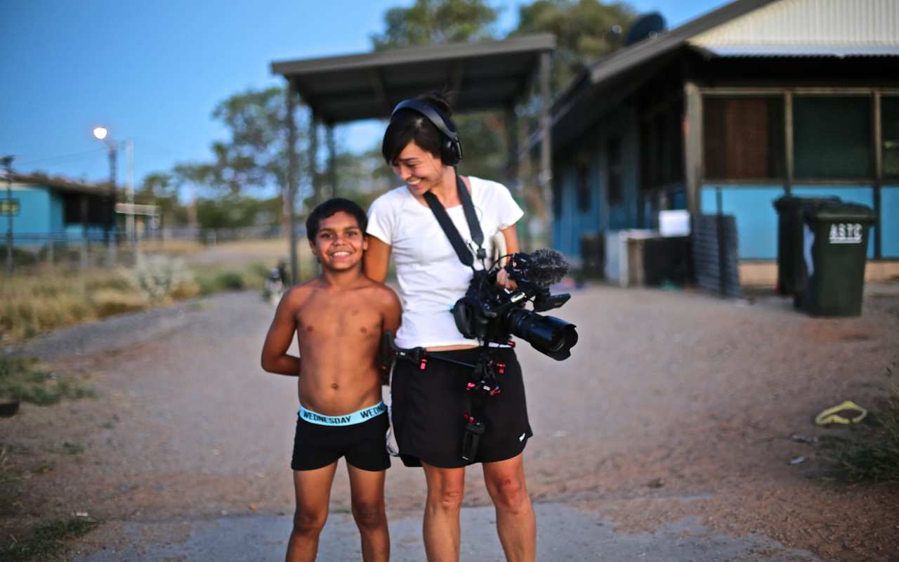 A young indigenous boy smiles with a member of the film crew from In My Blood It Runs