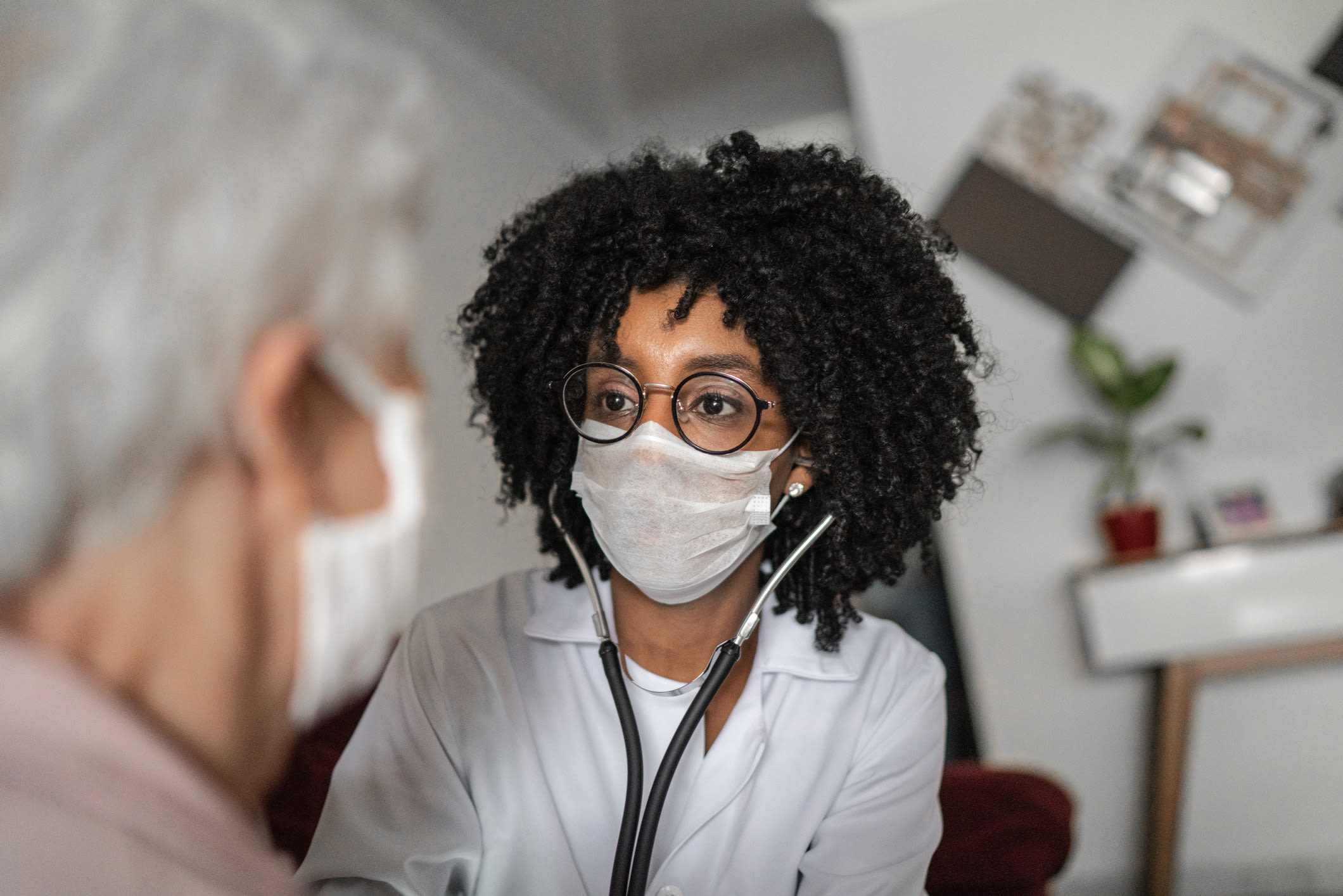 Doctor and patient wear face masks during consultation