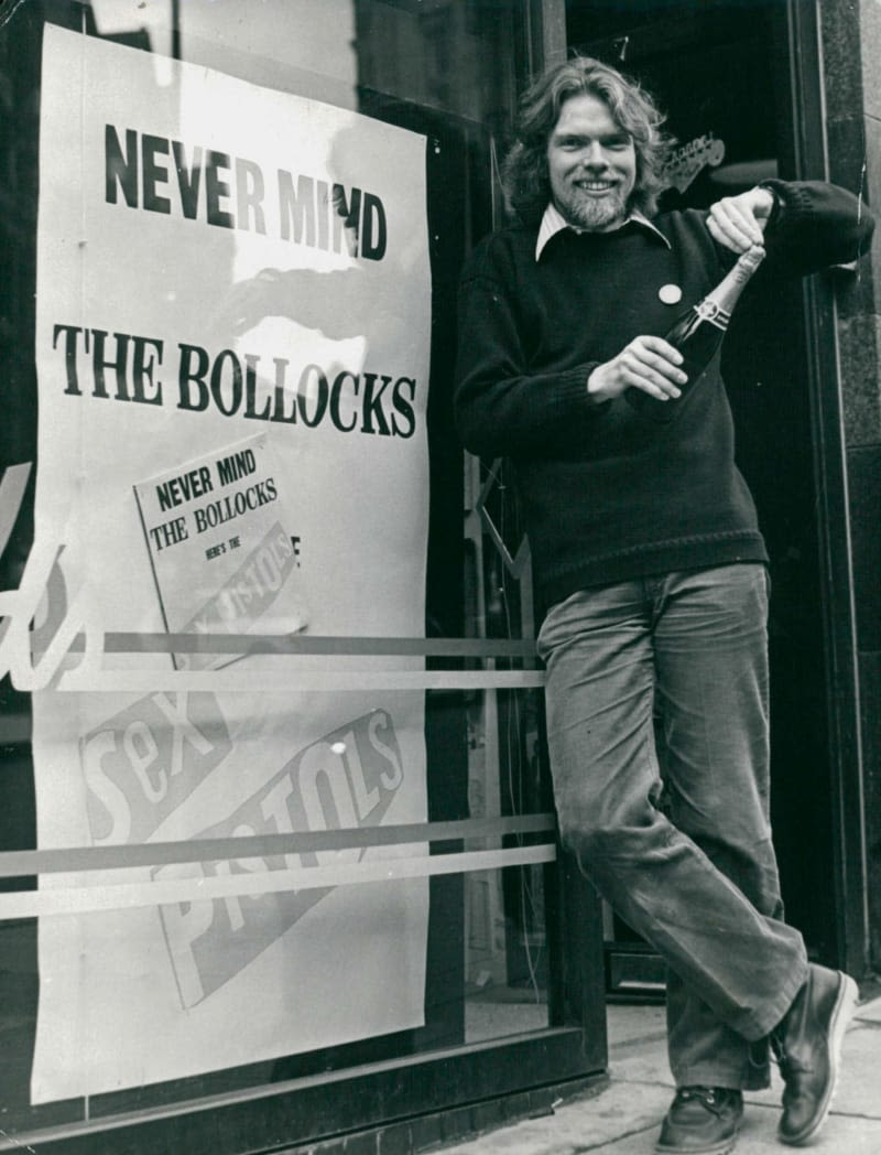Richard Branson holding a bottle of champagne in front of a sign that reads 'Never Mind The Bollocks'