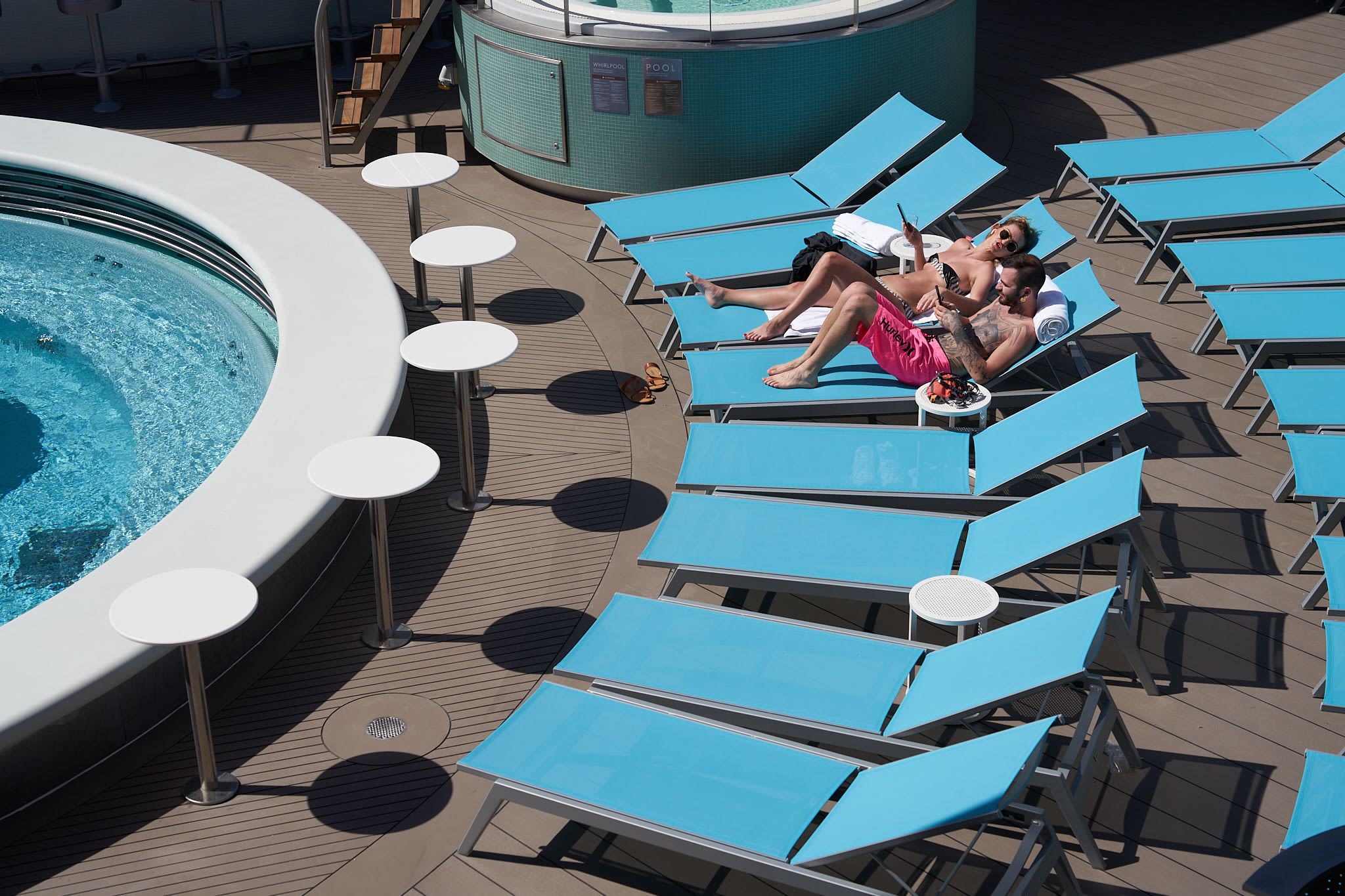 Two people laying on sun loungers by the pool on Virgin Voyages' ship Scarlet Lady