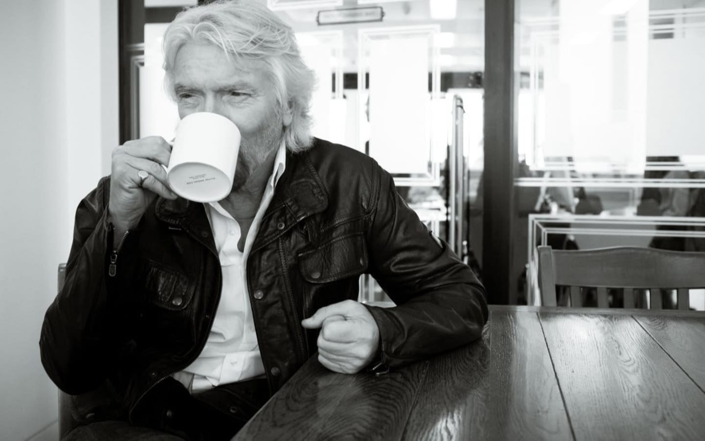 Black and white image of Richard Branson sitting at a table drinking from a mug