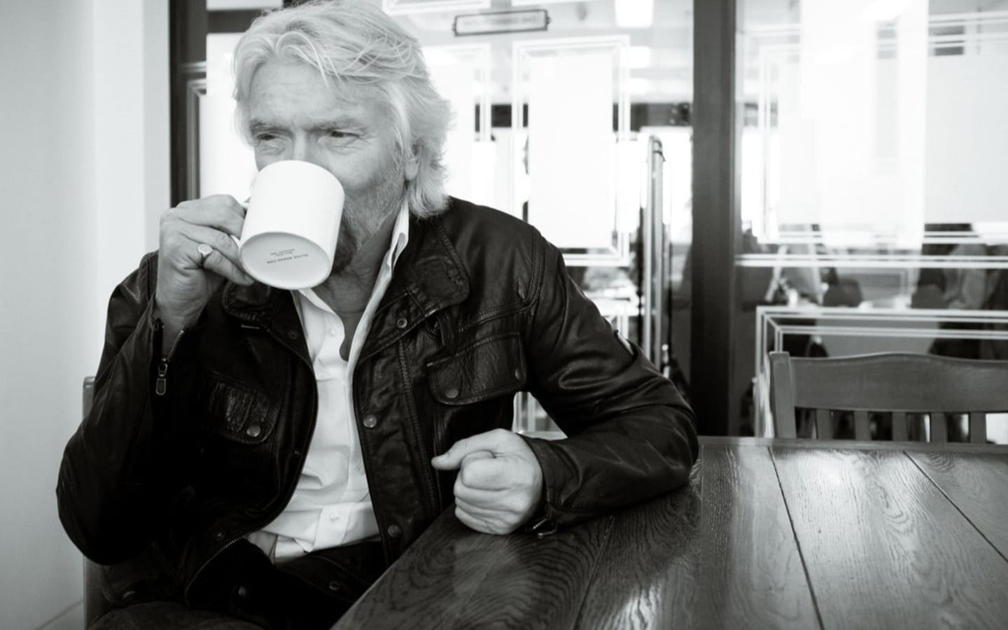 Black and white photo of Richard Branson in the office drinking tea