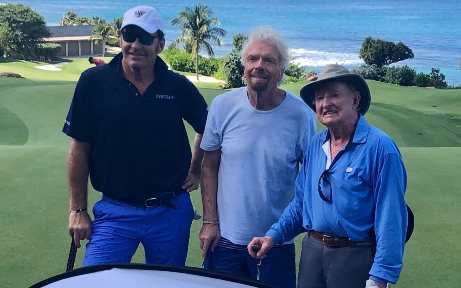 Richard Branson standing with Rod Laver and Nick Faldo on the golf course at Necker Island